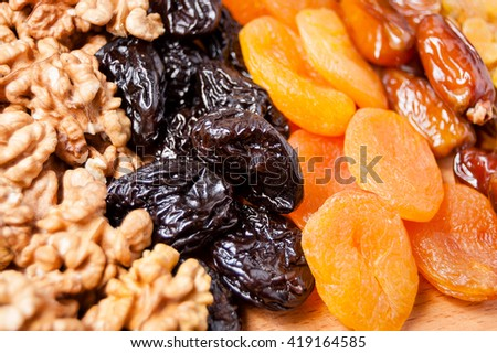 dried dates, figs, raisins, prunes, dried apricots and walnuts on a wooden board