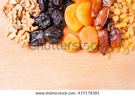 dried dates, figs, raisins, prunes, dried apricots on a wooden board, horizontal view