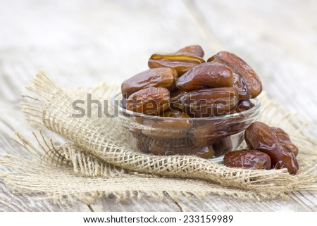 dried dates in a bowl on wooden background - stock photo
