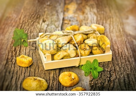 Dried figs - dry figs in wooden bowl on rustic background - stock photo