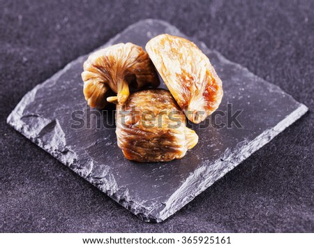 Dried figs over stone, black background, horizontal image
