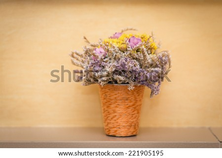 Dried flowers in basket placed in house - stock photo