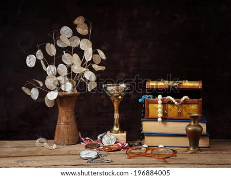 Dried flowers in ceramic vases and jewelry in a box on the table - stock photo