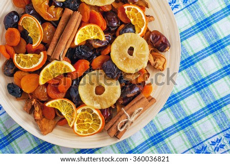 Dried fruits and cinnamon on a wooden plate on a napkin - stock photo