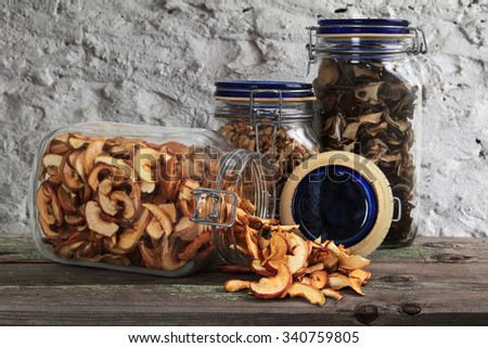 Dried fruits and nuts in a glass jar on a table - stock photo