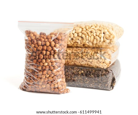 Dried fruits and nuts in transparent package over white: hazelnuts, cashew, roasted and salted peanuts, dried mulberry.