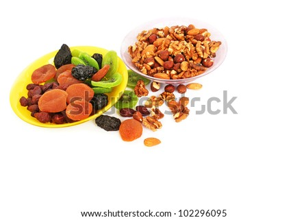 Dried fruits and nuts  in vases  isolated on white background.