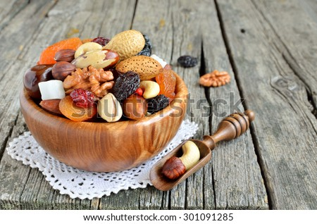 Dried fruits and nuts mix in a wooden bowl.