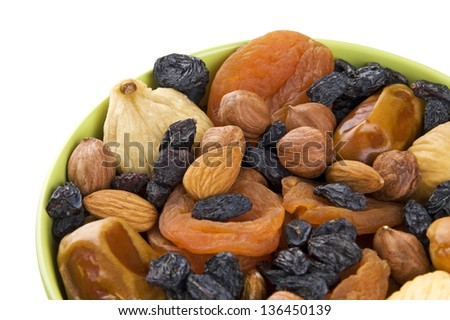 Dried fruits and nuts mixed in green bowl close up - stock photo