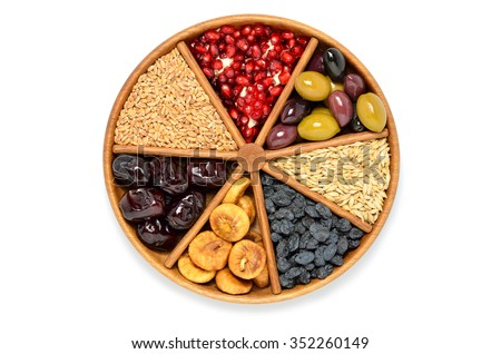 Dried fruits, barley, wheat, olives, pomegranate on wooden plate - symbols of judaic holiday Tu Bishvat .White background. Top view  - stock photo
