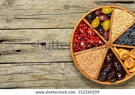 Dried fruits, barley, wheat, olives, pomegranate on wooden plate - symbols of judaic holiday Tu Bishvat .Copyspace background. Wood background. Top view  - stock photo