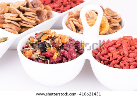 Dried fruits, berries and seeds in bowls closeup picture. - stock photo