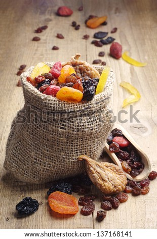 Dried fruits in a sack and spoon on the wooden table - stock photo
