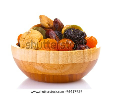 Dried fruits in wooden bowl isolated on white - stock photo