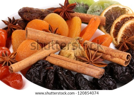 Dried fruits with cinnamon and anise stars on plate close-up