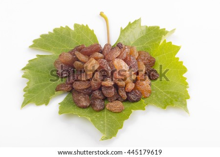 dried grapes raisins on white wood background with green grape leaf.top view