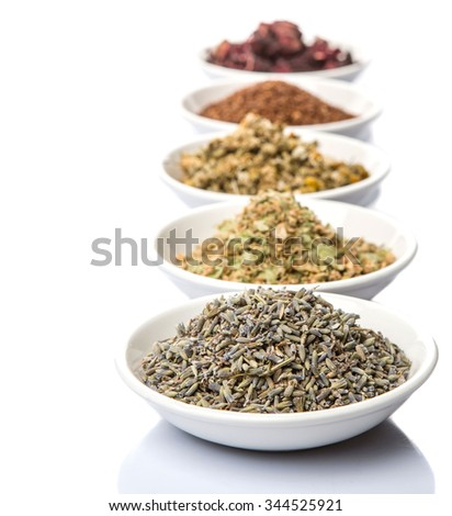 Dried herbal tea leaves, lavender, rooibos, chamomile, linden flower, hibiscus, Japanese green tea in white bowl over white background