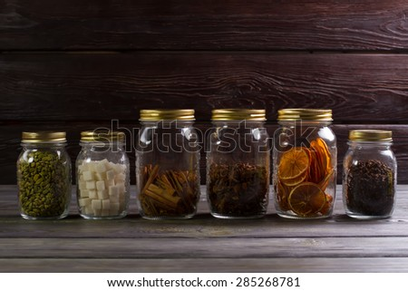 Dried herbs and spices in glass jars on wooden background.