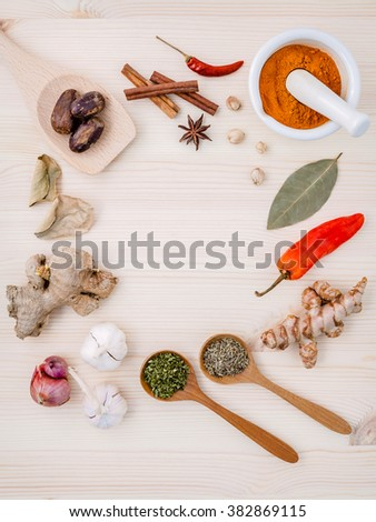 Dried herbs and spices nutmeg,star anise ,cinnamon stick,oregano,thyme ,ginger shallot,turmeric and chili on wooden table. Top view with copy space. - stock photo