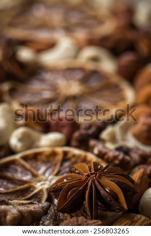 Dried herbs and spices on wooden background. Focused on anise star. Dried nuts, oranges and spices. - stock photo