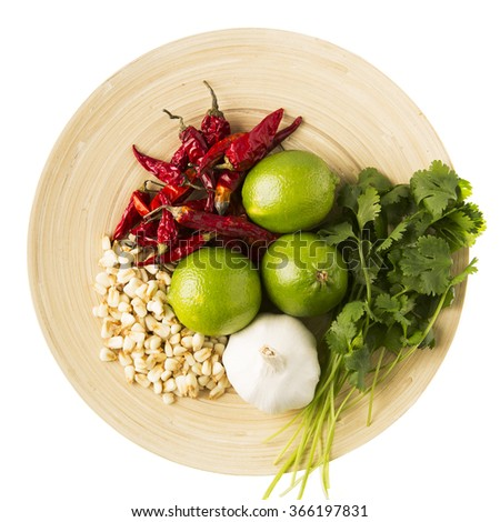 Dried hominy, garlic, lime, cilantro and hot peppers: ingredients for a version of a posole.  On wooden plate and isolated on a white background.