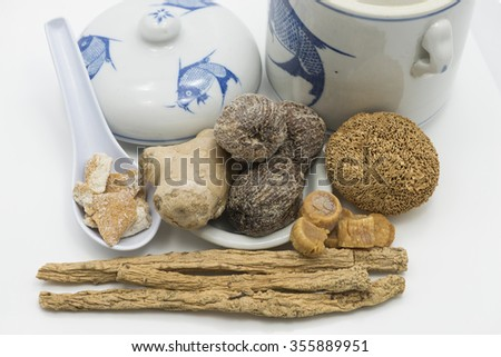 Dried ingredients used in Chinese herbal soup with health benefits. View are hericium, honey dates, ginger, citrus, scallops and codonopsis roots. Ingredients placed beside double boiling ceramic jar. - stock photo