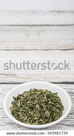 Dried Japanese green tea leaves in white bowl over wooden background