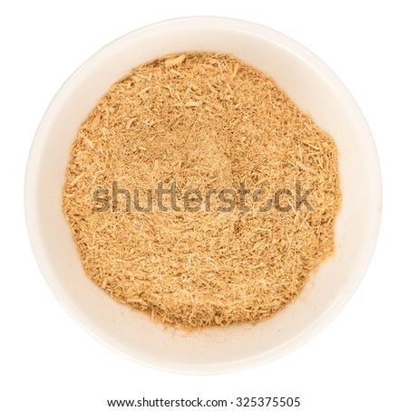 Dried lemongrass powder in a white bowl over white background