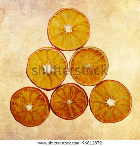 dried orange slices arranged in form of a triangle with grunge textured background