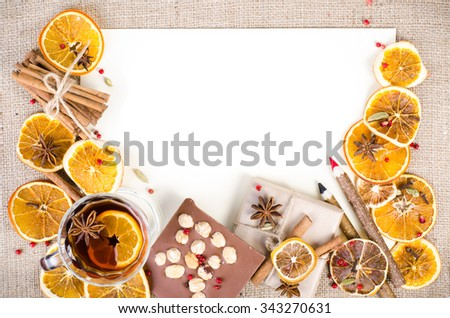 Dried oranges, cinnamon, cloves, cardamom, handmade milk chocolate with nuts, mulled wine, wooden pencil, list of paper on sackcloth, canvas. Christmas, New Year and winter. Free space for your text. - stock photo