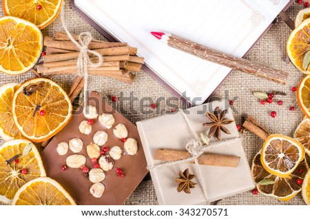 Dried oranges, cinnamon, cloves, cardamom, handmade milk chocolate with nuts, wooden pencil, list of paper on sackcloth, canvas. Christmas, New Year and winter.  - stock photo