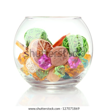 Dried oranges, wicker balls and other home decorations in glass bowl, isolated on white - stock photo