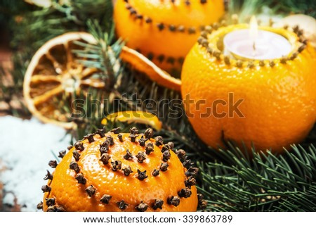 dried oranges with nuts and burning candles. Christmas decorations. Focus on the orange in the foreground - stock photo