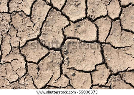 Dried out soil texture of a barren land - stock photo