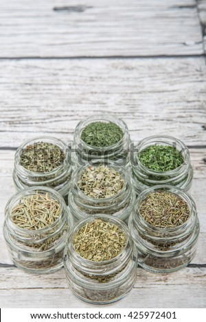 Dried parsley, estragon, marjoram, dill weed, rhyme, rosemary and basil herbs in mason jar over wooden background - stock photo