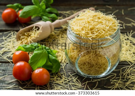 Dried pasta vermicelli, cherry tomatoes, basil, prepared for cooking. Selective focus