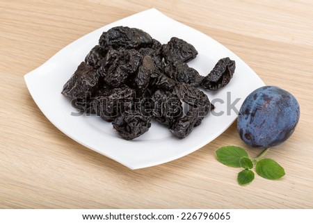 Dried plums in the bowl with fresh prune - stock photo