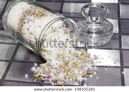 Dried potpourri with a natural fragrance to refresh the air in your home made from a mixture of natural flowers, plant shavings and spices spilling out of a glass jar onto a tiled grey surface - stock photo
