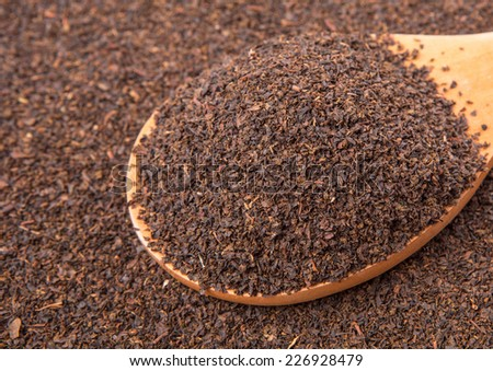 Dried, processed and blended tea leaves in wooden spoon - stock photo