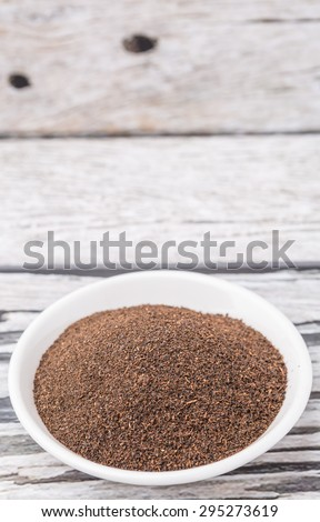 Dried processed tea leaves in white bowl over rustic weathered wooden background