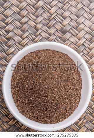 Dried processed tea leaves in white bowl over rustic wicker background