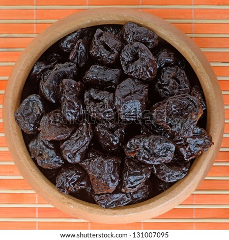 Dried prunes in wooden bowl on orange bamboo table cloth. - stock photo
