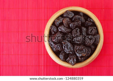 Dried prunes in wooden bowl on red bamboo table cloth. - stock photo