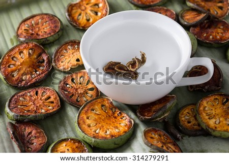 dried quince slices with cup on banana leaf - stock photo