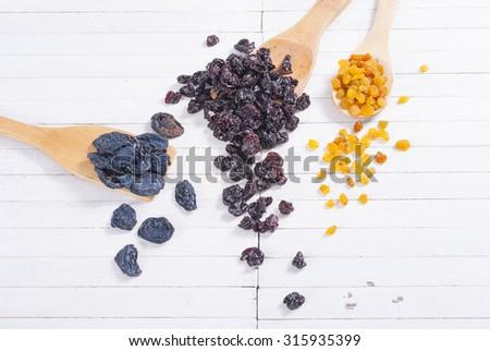 dried raisin cherry and plum fruits on white wood - stock photo