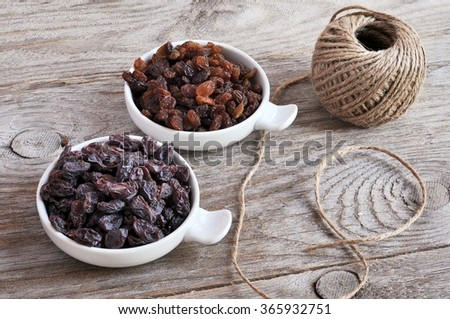 Dried raisins Turkish and Spanish (Malaga). Turkish raisins, Sultan raisins pitted . Raisins from Malaga with stones. Dried raisins on the wood backgraund - stock photo
