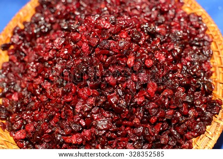 Dried red cranberries in a rustic bowl on blue table. Selective focus. - stock photo