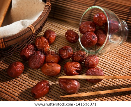 Dried red date or Chinese jujube. Traditional herbal medicine spill on bamboo mat. - stock photo