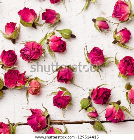 Dried rose buds on wooden table, background - stock photo
