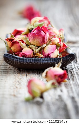 Dried rose buds on wooden table, selective focus - stock photo